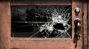 a glass door with a big smash in it where someone tried to break in.