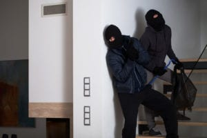 two men in ski masks sneaking into a building to steal