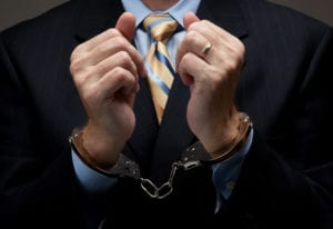 close up of a man in a business suit wearing hand cuffs