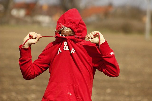 A woman trying to hide her face by pulling the strings of her hoodie tightly to make the face hole very small.