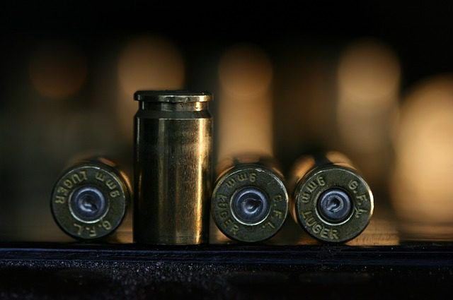 A close up picture of four bullets, three lying on their side and one standing up. The reference is Michigan's firearm rights and gun laws.
