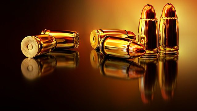 A close up picture of bullets against a golden and black background, signifying the use of firearms, and the subject of gun laws in Michigan.