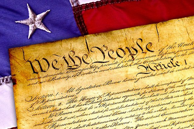 A close up picture of the US Constitution, laid against the American flag, signifying the importance of the Constitution to the American people.
