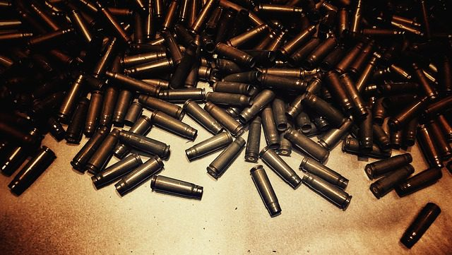 A huge pile of bullet casings, which references the issue of gun safety in Michigan.