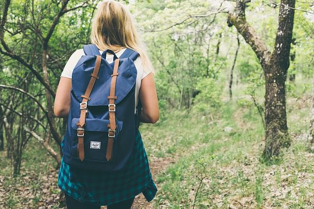 A young girl walking away from the camera with a backpack on her back, signifying a teen runaway.