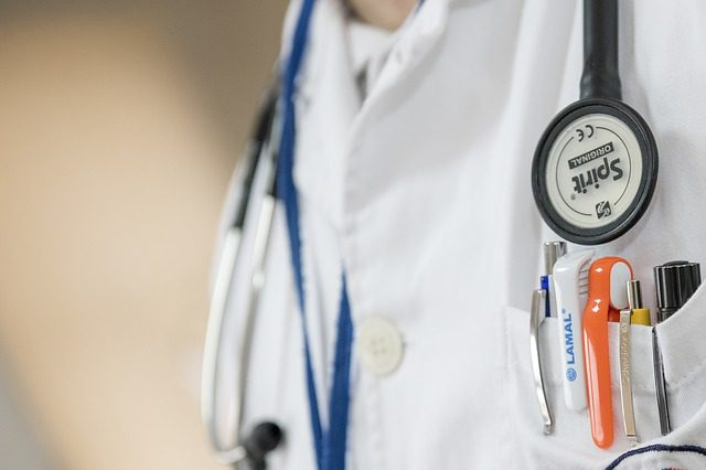 A close up of a doctor's lab coat pocket, containing several pens and with a stethoscope hanging over his shoulder.