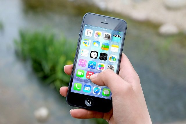 A hand holding up a smartphone with a screen full of apps visible. The person is about to select an app by touching it with their thumb.