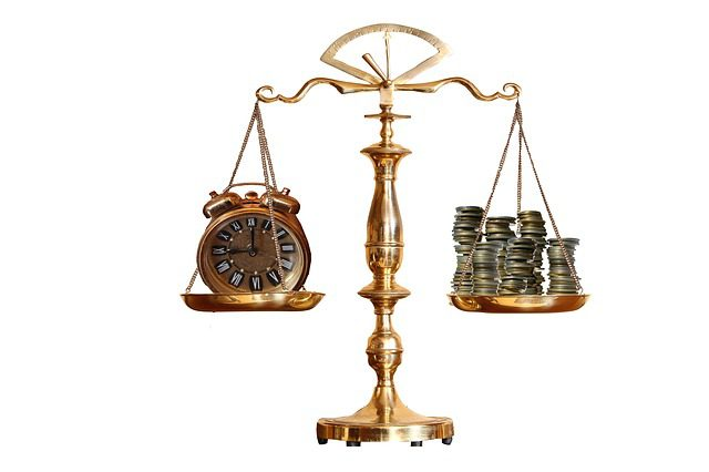 A picture of a scale with a clock on one side and a pile of coins on the other.