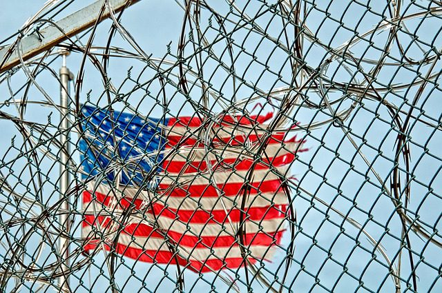 A tattered American flag viewed through the coils of razor view on top of a prison fence.