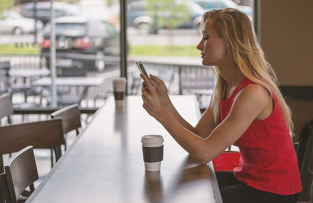 A woman sitting at a counter in a coffee shop looking at something on  her phone while she drinks a cup of coffee.