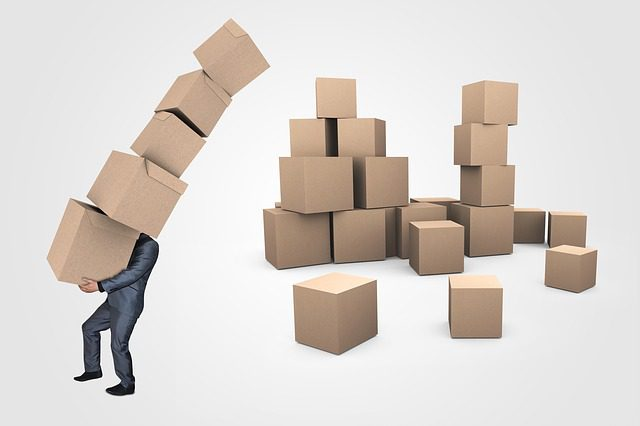A picture of a person carrying a big tack of boxes, with a large pile of boxes still piled up behind them.