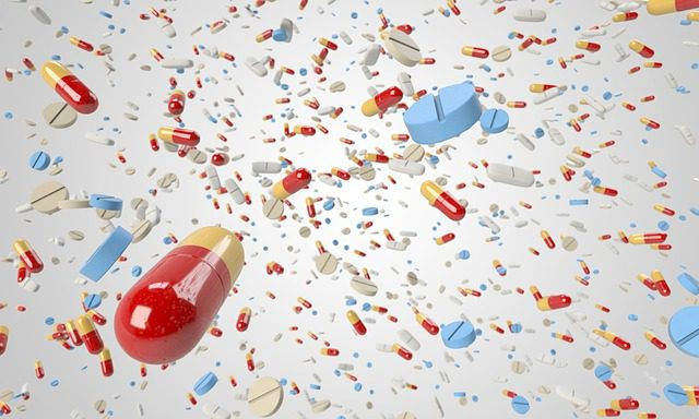 A view of many different types of pills raining from the sky