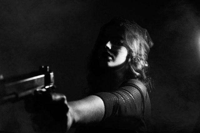 A woman holding a gun out in her hand, pointing it at someone.