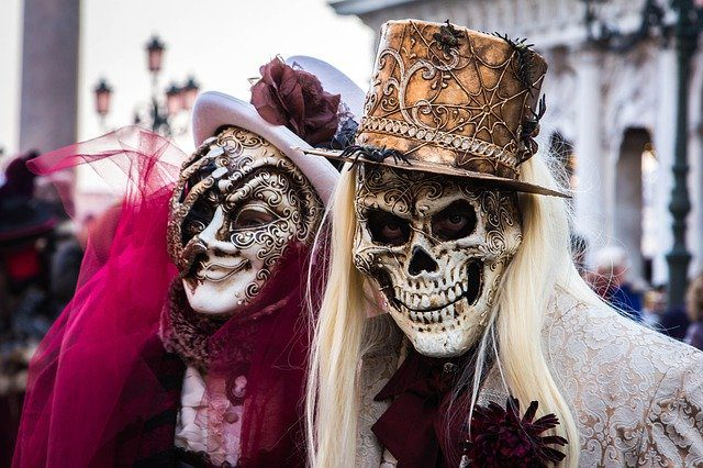 Two people in masks and costumes at a carnival