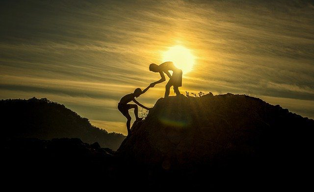 A silhouette of one person helping someone up onto the top of a mountain with a sunrise in the background.