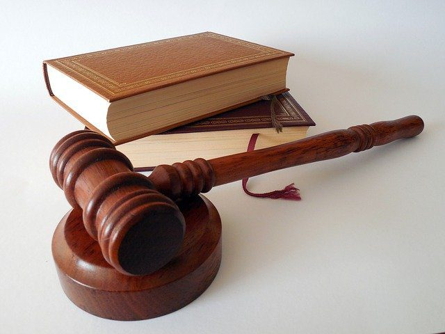 A close up of two books in a stack next to a Judge's gavel, which symbolizes the law and the practice of being a lawyer.