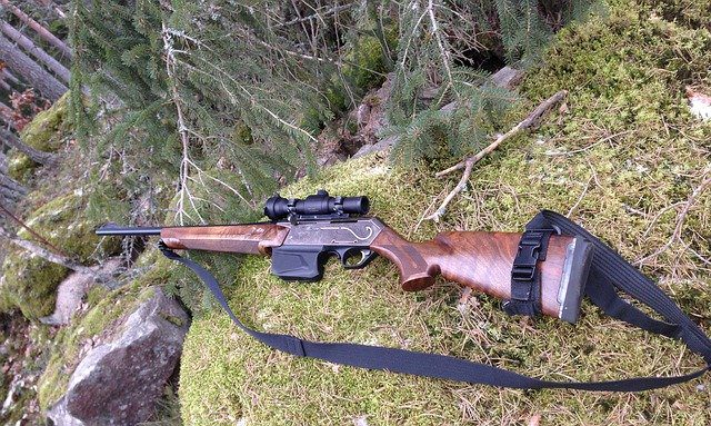 A hunting rifle laid across some mossy rocks in the woods