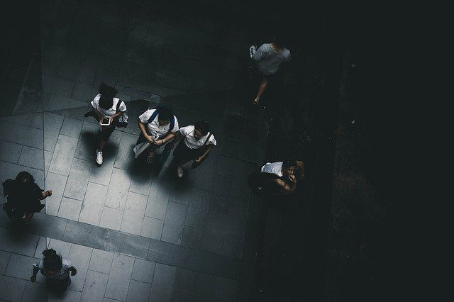 A bird eye view of students walking in a dark plaza