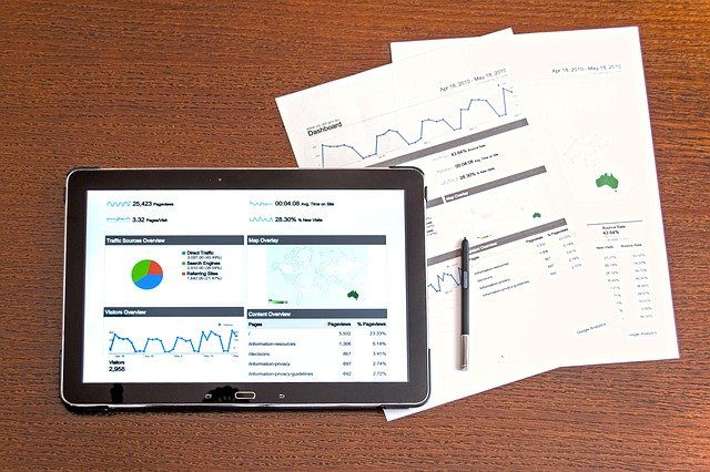 A tablet open to a screen showing an analysis of data, and a pile of printed sheets, showing similar data, graphs and charts.