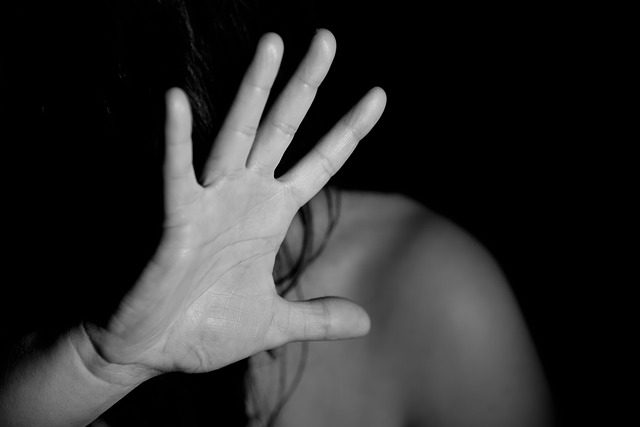 A black and white image of a woman protecting her face with her hand against an assault