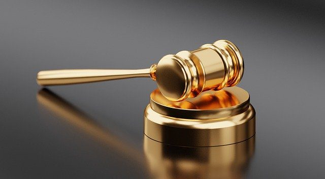 A golden Judge's gavel against a simple grey background