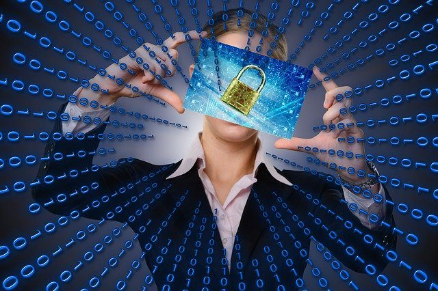 A picture of a woman holding a screen with a lock on it in front of her face.  Binary code is flowing out all around her.