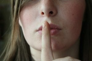 Close up of a woman's face holding her finger to her lips for silence