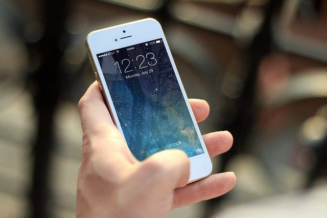A close up of a hand holding a cell phone.