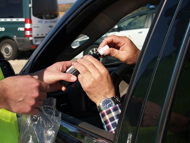 A close up of a person's hands, while they sit in their car, taking a breath test machine from an officer