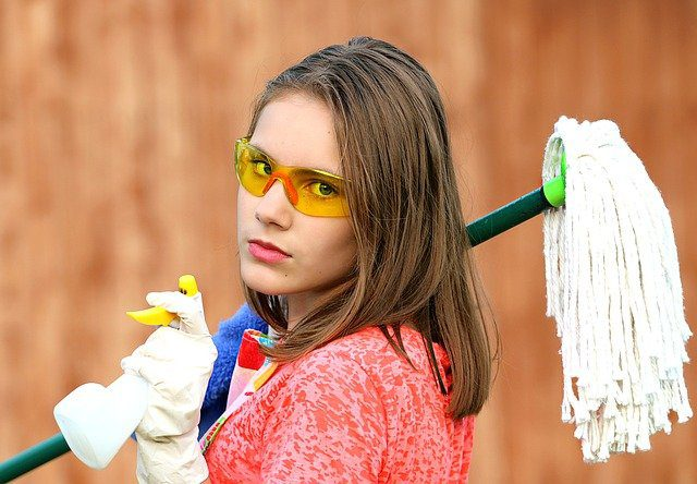 A young woman looking at the camera and carrying a lot of cleaning supplies, symbolic of a clean slate.