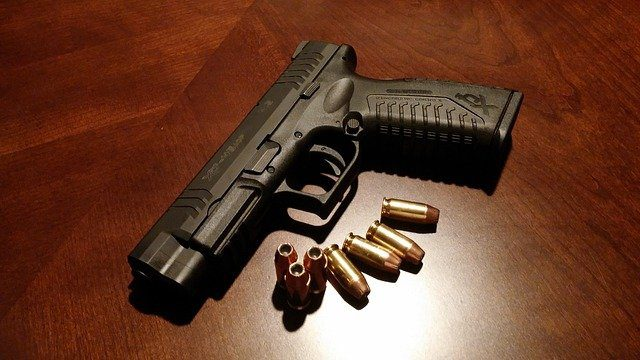 A handgun with seven bullets lying on a wooden table top.