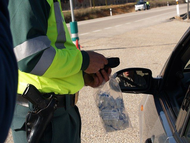 A police officer standing next to a car, collecting a breath sample from a driver through the window