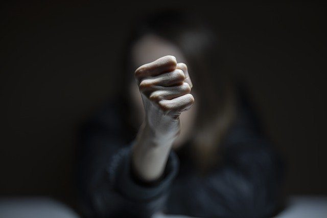 A woman's fist being held up in front of her face. The fist is clear and focused, but the face is blurry and in shadow.