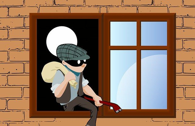 A cartoon of a masked man slipping through a window with a bag of stolen loot over his shoulder