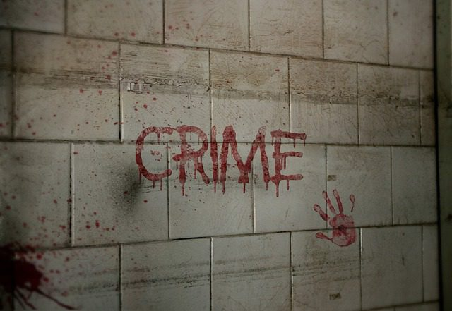 """A dirty wall at a crime scene, with a bloody handprint, some blood spatter, and the word """"crime"""" scrawled on the tile in blood, symbolizing violence and criminal activity."""