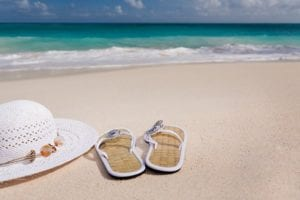 Hat and sandals on the beach
