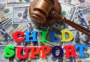 """Letters spelling""""Child Support"""" sittong on top of a stack of cash next to a judges gavel"""