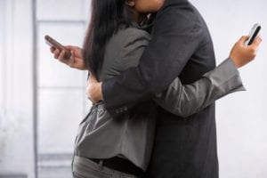 Couple embracing while looking at their phones
