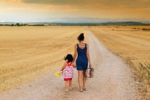 Mother and daughter walking down dirt road