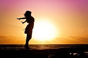 Woman pretending to fly in front of sunrise
