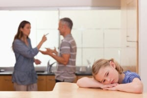 Couple arguing in front of sad child