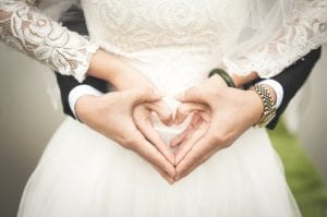 Newlyweds making heart sign with hands
