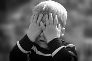Young boy covering face with hands