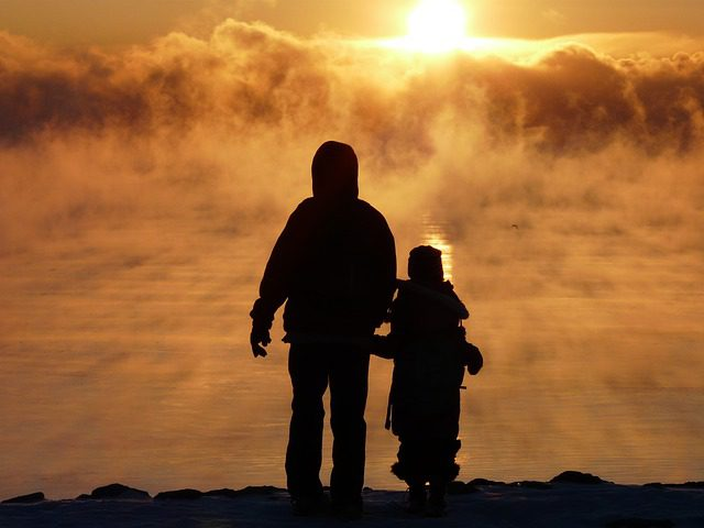 Parent and child watching sunrise
