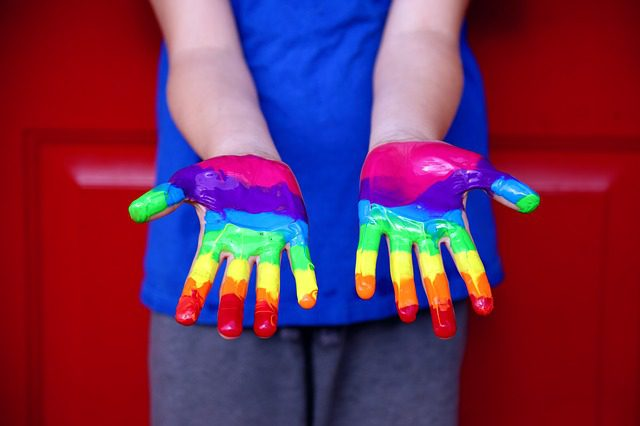 A young person's hands covered in rainbow colored paint, signifying gay pride.