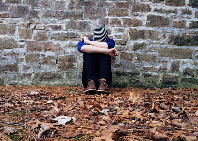 A sad teen, sitting against a wall outside, with their arms folded across their knees and their head down.