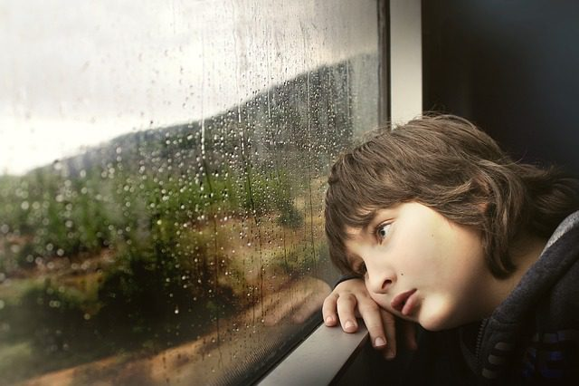 A young boy sitting at a window, watching the rain with a sad look on his face.