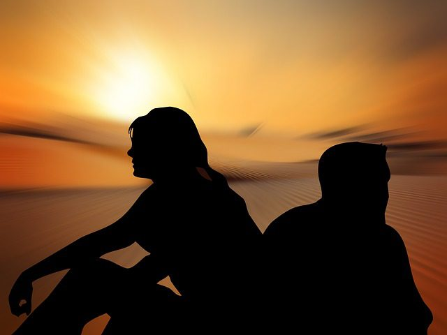 Silhouettes of a man and woman sitting back to back in front of a sunset.