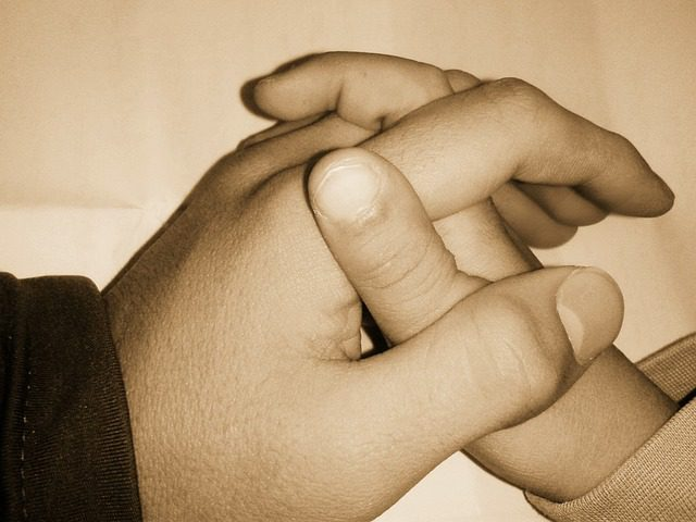 A close up sepia toned picture of an adult's hand holding a child's hand.