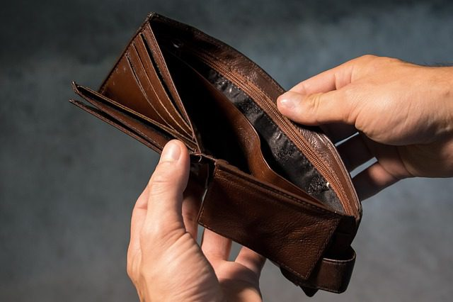 A man's hands holding a leather wallet open that is completely empty.